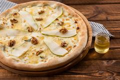 Traditional pizza with pear, nuts and blue cheese on a wooden background. Close up. Top view. royalty free stock photo