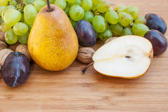 Pear, plums, nuts and green grapes on wooden background Royalty Free Stock Photos