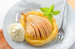 Pear on puff pastry. Pear with honey on puff pastry, served with cream and mint leaves Stock Photos