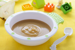 Pear puree in bowl. For baby nutrition and some toys Stock Photos