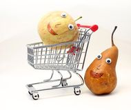 Pear pushes the shopping cart with an apple with eyes Royalty Free Stock Image