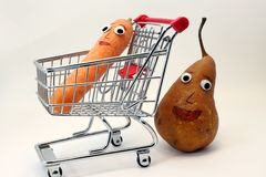 Pear pushes the shopping cart with a carrot Royalty Free Stock Image