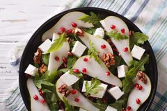 Pear salad with pomegranate and arugula close-up. horizontal top. Pear salad with pomegranate, feta and arugula close-up on a plate. horizontal top view stock image