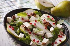 Pear salad with pomegranate, cheese and arugula close-up. horizo Royalty Free Stock Photos