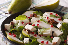 Pear salad with pomegranate, cheese, walnuts and herbs closeup Royalty Free Stock Photo