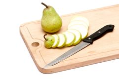 Pear and slices with knife on chopping board Stock Images