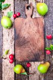 Pear and small apple around empty cutting board on wooden rustic background. Top view. Frame. Autumn harvest. Copy space. Stock Photography