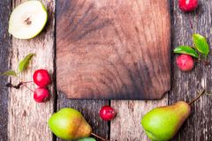 Pear and small apple around empty cutting board on wooden rustic background. Top view. Frame. Autumn harvest. Copy space. Royalty Free Stock Images