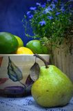 Pear Still Life. This is a still life photograph of a pear with limes and a lemon, blue flowers, blue background and a bowl with leaves set up on it Royalty Free Stock Image