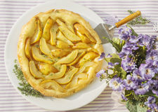 Pear tart with thyme on purple table summerly flowers Stock Images