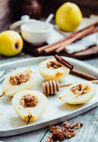 Pear with walnuts and honey before baking, cinnamon sticks Stock Photo