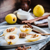 Pear with walnuts and honey before baking, cinnamon sticks Royalty Free Stock Image