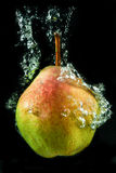 Pear in water. Sinking pear in water, bubbles, Tasty royalty free stock image