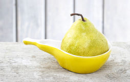 Pear in yellow ceramic plate of pear shape Royalty Free Stock Photography