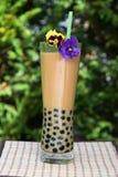 Pearl в чае молока и оформлении цветков pansy Стоковая Фотография RF