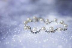 Pearl серебряный браслет с диамантами на расплывчатой голубой предпосылке Стоковое Изображение RF