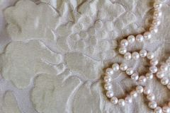 Pearl background with beautiful silk texture and string of natural rose pearl necklace royalty free stock images