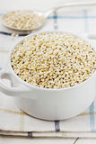 Pearl barley. In a white ceramic bowl on a wooden background Stock Photography