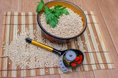 Pearl barley in a cup, nearby a spoon and a centimetric tape. Pearl barley in a cup, nearby a wooden spoon and a centimetric tape Stock Photo
