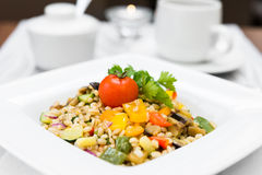 Pearl barley porridge with vegetables on square plate Royalty Free Stock Images