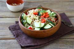 Pearl barley salad with vegetables in a wooden bowl Royalty Free Stock Photo