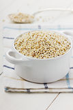 Pearl barley in a white ceramic bowl. On a wooden surface (selective focus Stock Photos