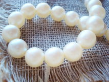 Pearl bead. On the grey flax rag royalty free stock photography