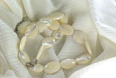 Pearl beads. White pearl oval beads on white fabric Royalty Free Stock Photos