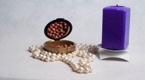 Pearl beads, a box of rouge and purple square candle Stock Photo