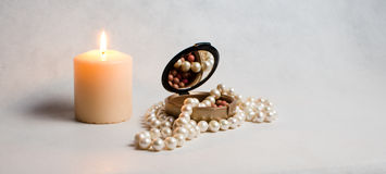 Pearl beads, a box of rouge and white round burning candle Royalty Free Stock Photo