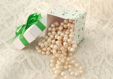 Pearl beads falling out of the gift box on a lacy surface Stock Images