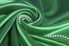 Pearl beads on green silk. Luxurious deep green satin/silk folded fabric Royalty Free Stock Photo