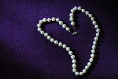 Pearl beads in heart shape on purple velvet background Royalty Free Stock Photos