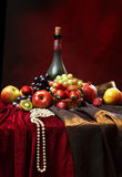 Pearl beads lie on the edge of the table, classic Dutch still life with dusty bottle of wine and fruits on a dark red background,. Vertical Royalty Free Stock Photo