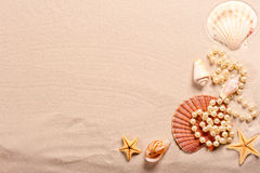 Pearl beads and seashells in sand Stock Photos