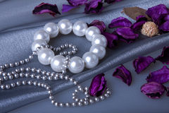Pearl bracelet. And flowers behind silver organza Stock Images