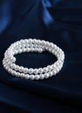 Pearl bracelet. On a silk blue fabric stock photos