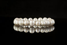 Pearl bracelet on a black mirror surface Stock Image
