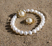 Pearl bracelet and earrings lying. On the sand in the sun royalty free stock images