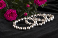 Pearl bracelets and bouquet of roses. Antique bronze bell and bouquet of roses pearl bracelets and bouquet of roses on a black background Stock Photography