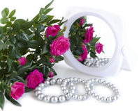Pearl bracelets, bouquet of roses and a mirror. On a white background Stock Photo