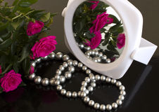 Pearl bracelets, bouquet of roses and a mirror. On a black background Royalty Free Stock Photography