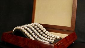 Pearl bracelets in brown wooden casket, jewelry made of pearls, Pearl bracelets on a pedestal decoration for glamorous stock video