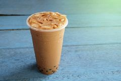 Pearl Bubble milk tea with ice in plastic cup on wooden. Floors stock photos