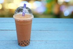 Pearl Bubble milk tea with ice in plastic cup on wooden. Floors royalty free stock image