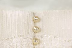 Pearl buttons on ivory wedding dress. Closeup of pearl buttons on an ivory wedding dress Royalty Free Stock Images
