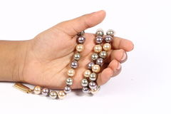 Pearl chain in the hand. Different color pearl chain in the hand Royalty Free Stock Photo