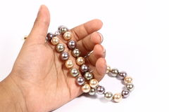 Pearl chain in the hand. Different color pearl chain  in the hand Royalty Free Stock Photos