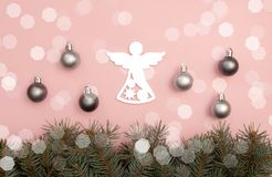 Pearl Christmas balls and figure of angel on the pink background with pine tree branches stock image