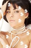 Pearl desire puzzle. Puzzle portrait of mysterious brunette with white pearls Stock Photography